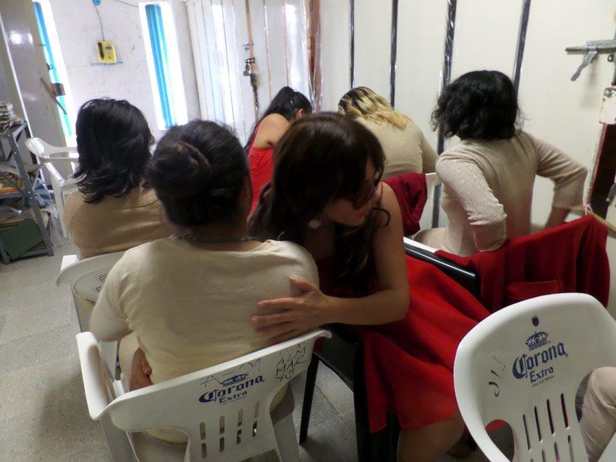 Despedida tren. Fotografía que documenta el performance hecho con mujeres en reclusión. Descripción: Mujeres sentadas en fila en un aula de castigo diciéndose secretos.