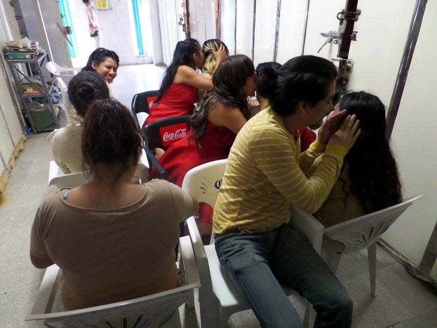 Lo mejor del tren. Fotografía que documenta el performance hecho con mujeres en reclusión. Descripción: Mujeres sentadas en fila en un aula de castigo diciéndose secretos.